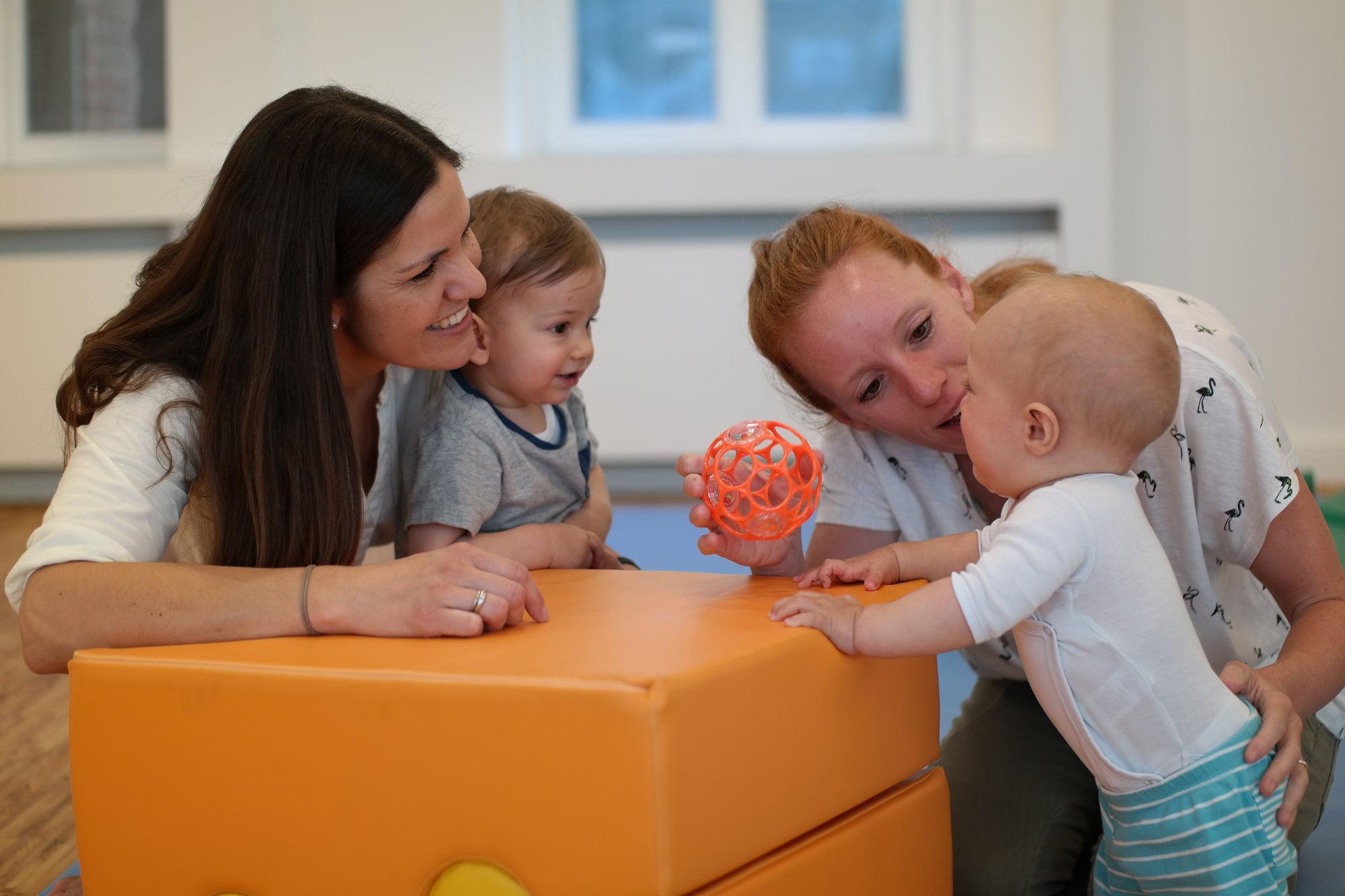 Zwei Mütter und zwei stehende Babys im Babys erstes Jahr Kurs mit OBall