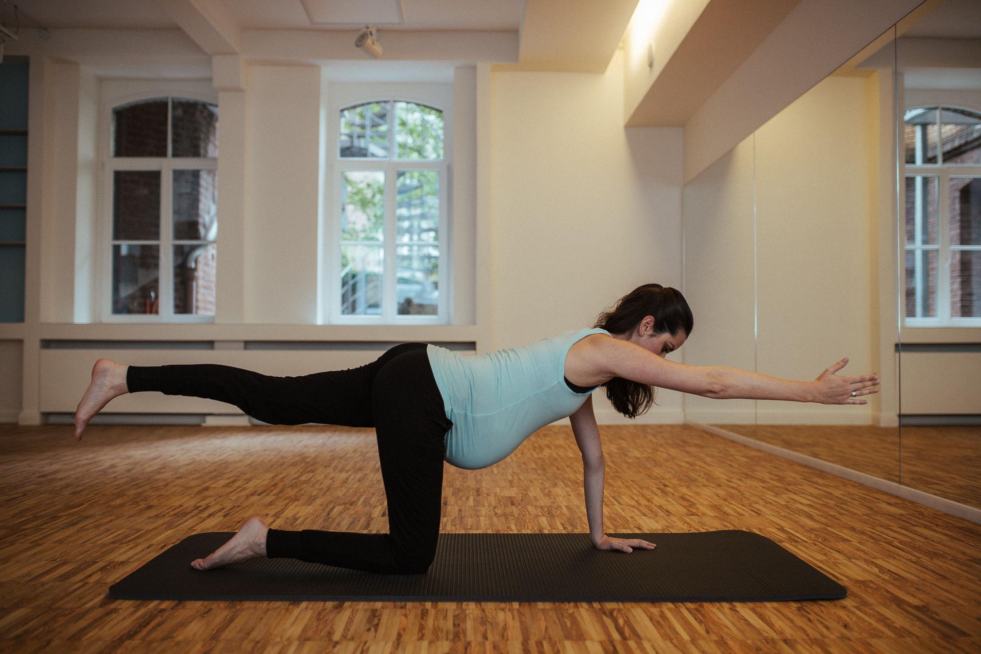 Schwangere Frau macht eine Pilates Übung auf einer Matte.
