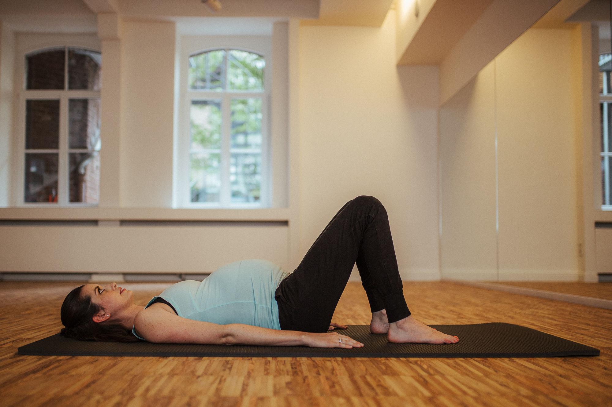 Schwangere Frau liegt auf einer Pilates Matte.