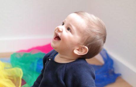 Baby schaut beim Vorsingen gespannt nach oben und hat Spaß beim Babys erstes Jahr Kurs.