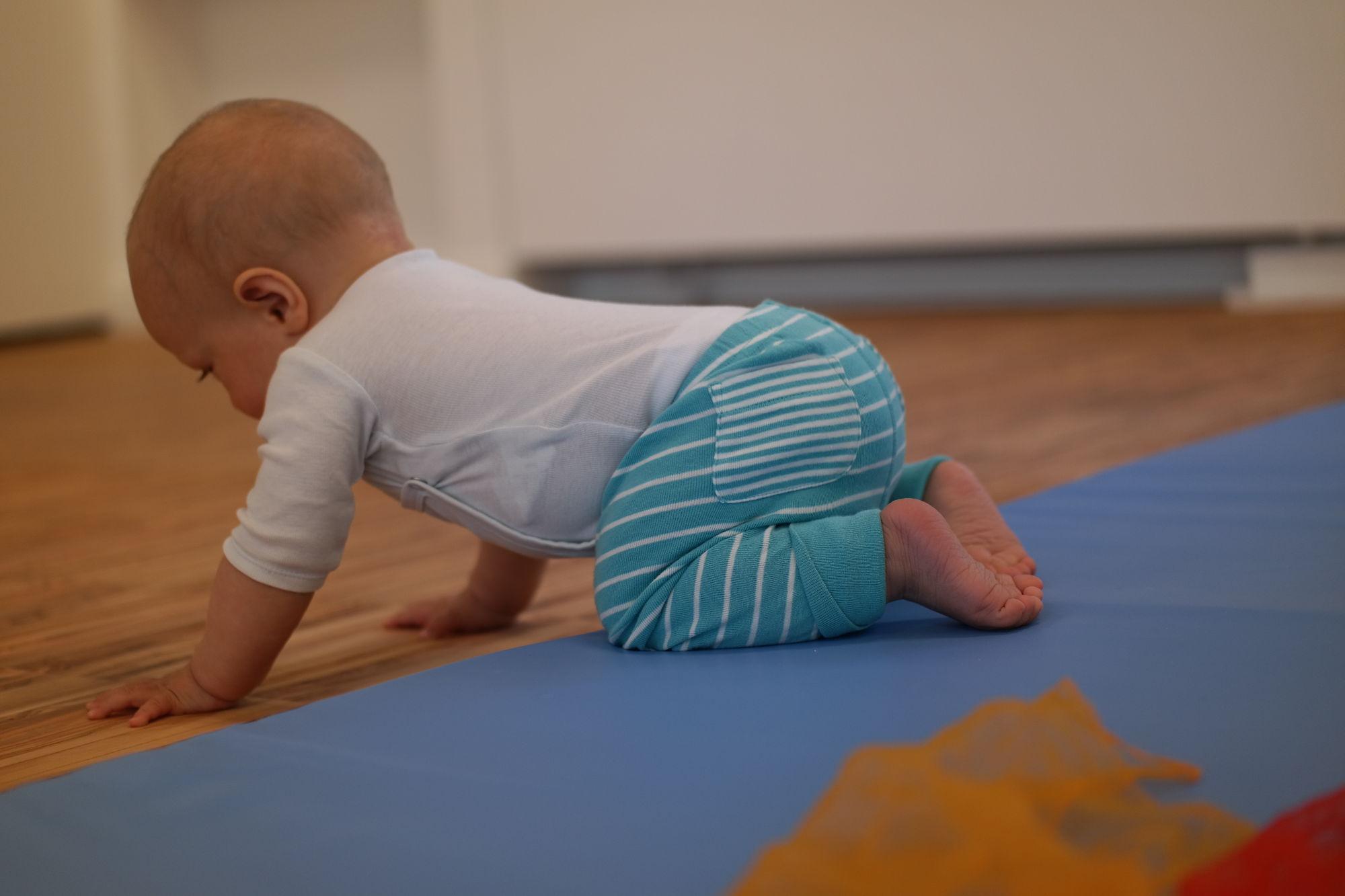 Baby im Kursraum schaut sich interessiert den Boden an