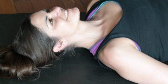 Frau liegt auf einer Pilates Matte.