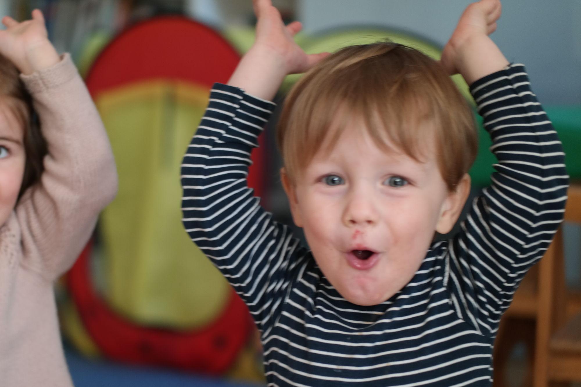 Junge wirft fröhlich seine Hände in die Luft