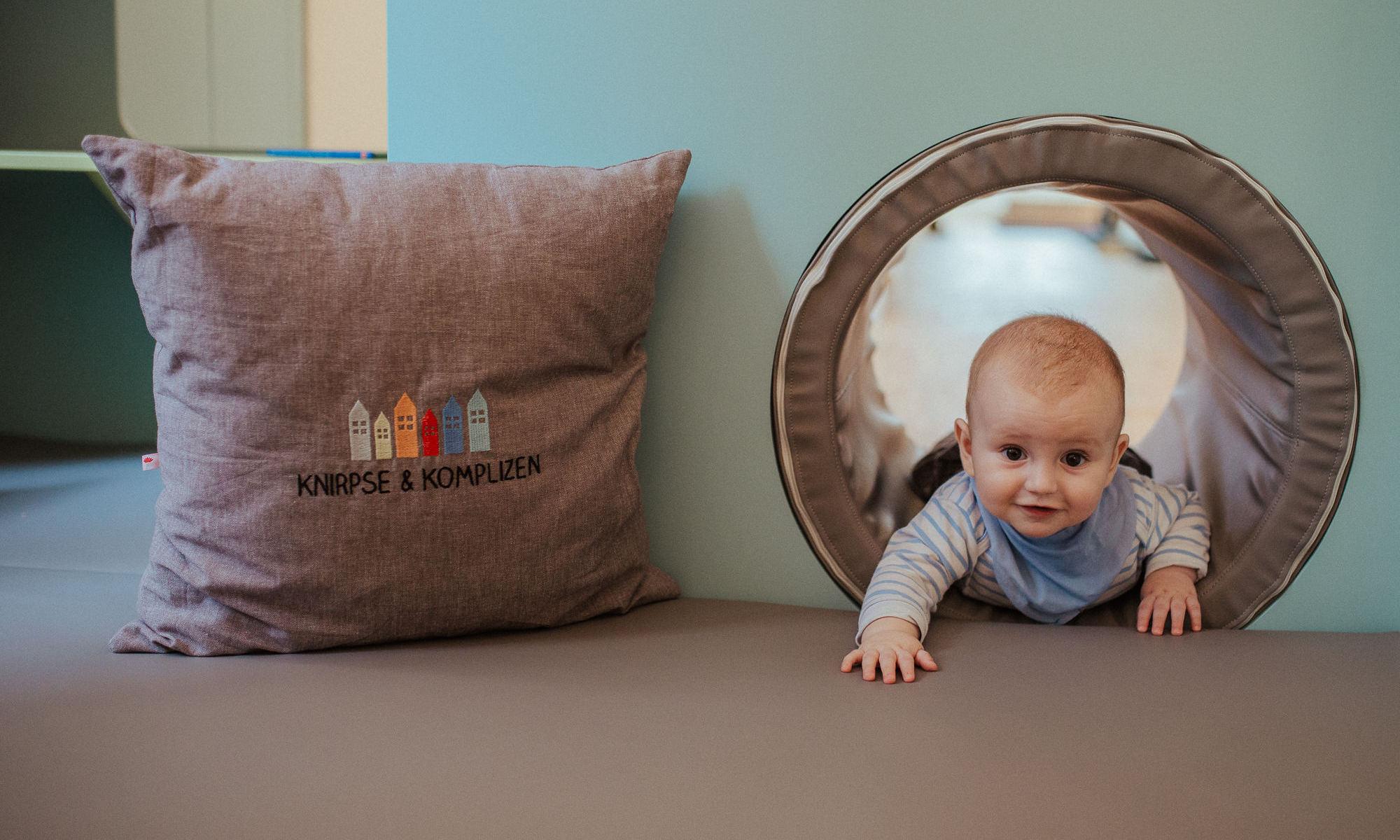 Baby schaut aus dem Tunnel der Spiel- und Krabbelecke