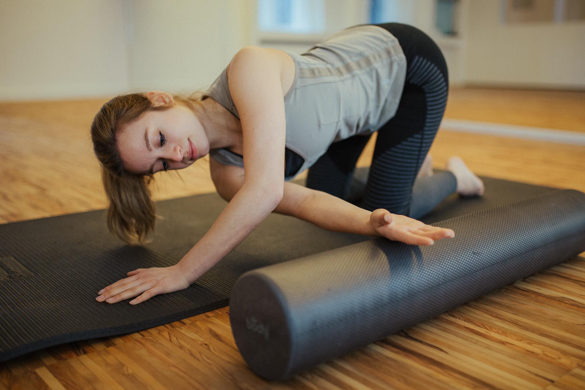 Frau trainiert mit Pilates Rolle