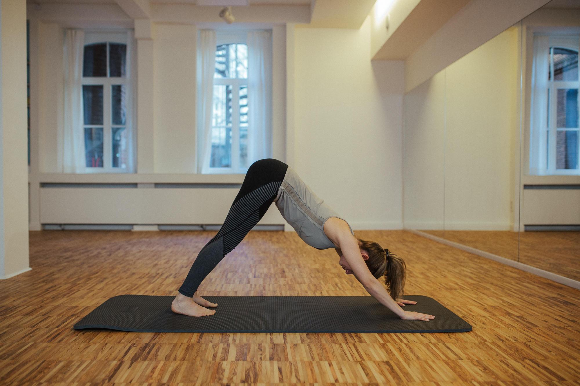 Frau in Yoga Pose herabschauender Hund.