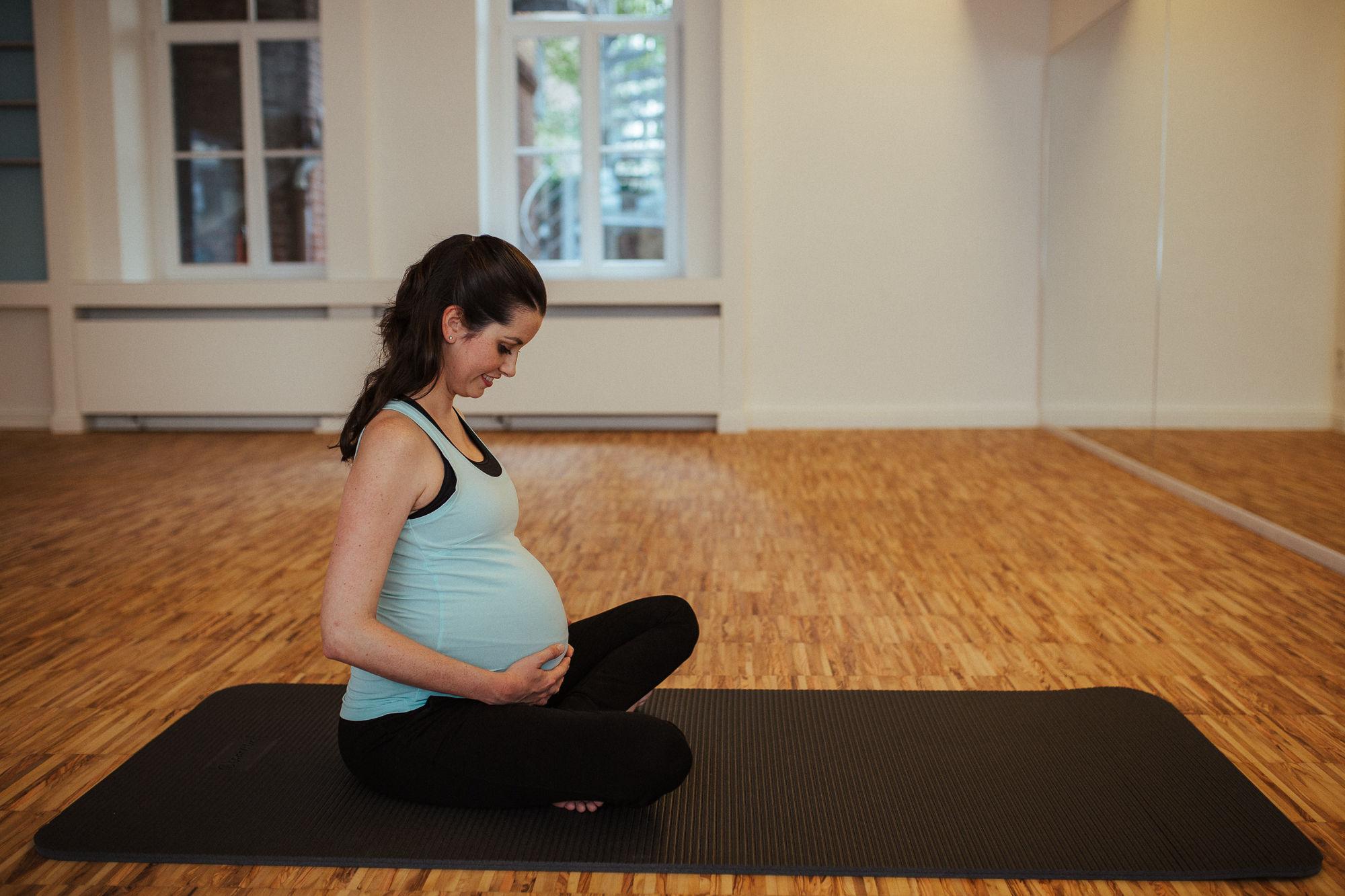 Schwangere Frau sitzt auf einer Pilates Matte und hält die Hände auf ihrem schwangeren Bauch.
